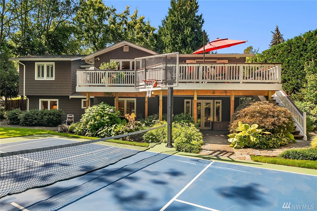Private Medina home in park-like setting. Remodeled in 2007 amidst gorgeous landscaping. Open-concept great room w/ kitchen, dining & large TV room. Honed slab countertops, Wolf 5-burner cooktop, butcher block island. French doors lead to sunny deck that offers total privacy. Master w/ ensuite bath, walk-in closet, and office on main. 3 bedrooms and bonus room down. 2 fireplaces, 2-car garage, sports court. Rare secluded retreat that, minutes from parks, beaches, golf and quick morning commute.