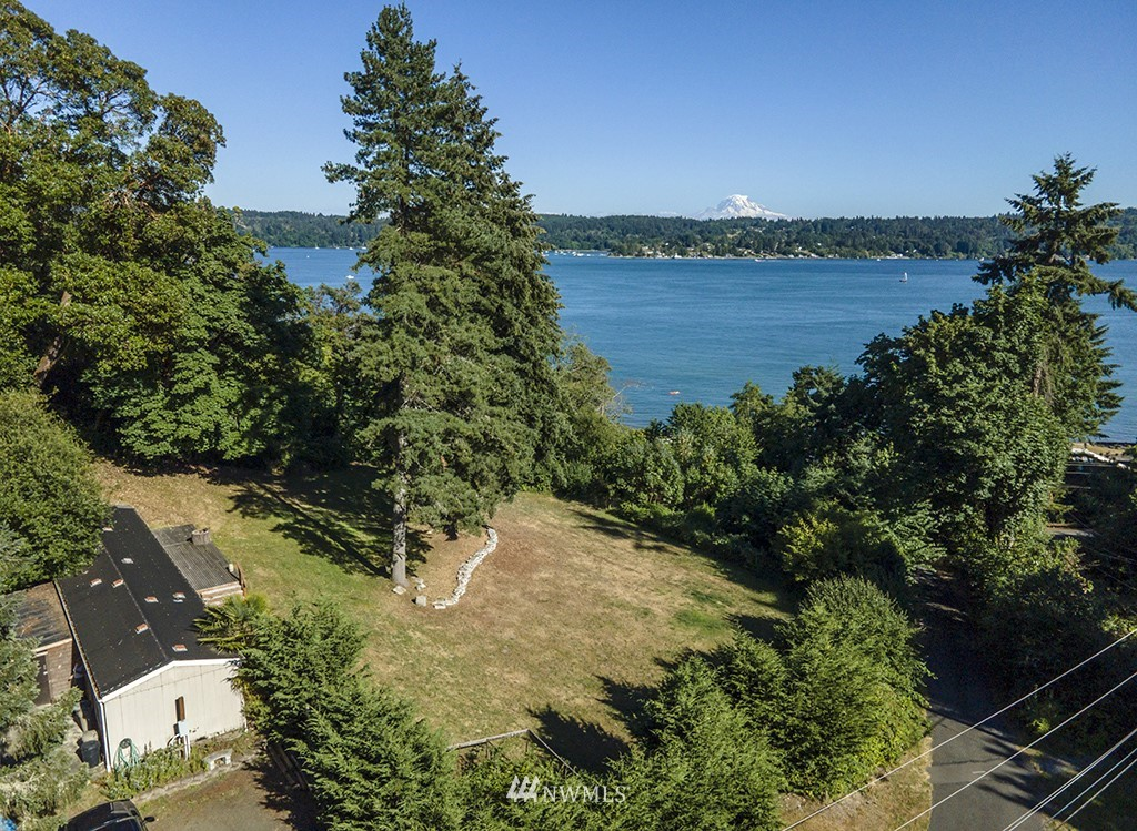 Build your dream home and live on-site while building your island paradise! Located in upper Burton, this private, 10.98 ac home site is buffered by a deep ravine protecting views of Quartermaster Harbor & Mt. Rainier. You're half way there to development with an installed well, 4 bdrm septic, 924 sq. ft. 1995 manufactured home & a separate garage w/water situated privately on the upper portion.  Near coveted Burton with nearby beaches, coffee & general store. MIL/ADU potential.