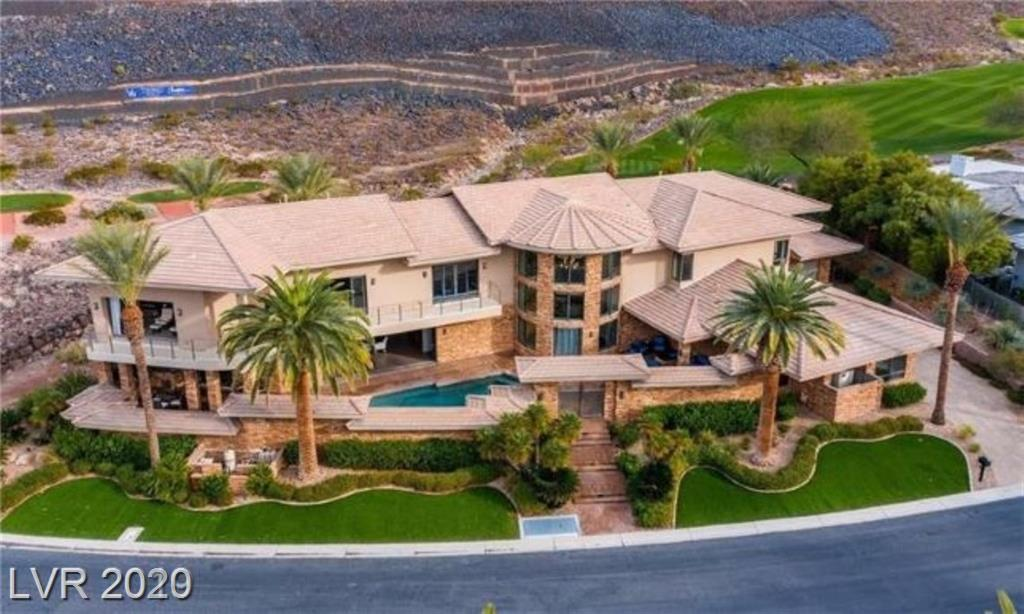 Magnificent MacDonald Highlands home located on the 13th hole of the Dragon Ridge Golf Course. Incredible panoramic views of the city/Strip, mountains and golf course. This property was filmed in a popular Las Vegas movie. 7200 SF that includes 4 bedrooms, 6 bathrooms, 2 laundries, 5 car garage, gym, theater, and chef,s kitchen. All bedrooms feature full bath rooms, walk in closets and a private deck/patio spaces. The property offer great indoor/ outdoor entertaining inclusive of a courtyard with private pool, outdoor kitchen and fire pit.