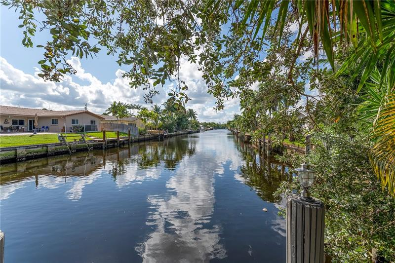 Forever Water Views from this Fantastic 2/2 Ocean Access Waterfront Pool Home in Highly Desirable Coral Ridge Isles! Enjoy waterfront life & water/sunset views from every room. Split bedroom floor plan w/primary en-suites at either side. Updated kitchen w/granite counters & Bosch cooktop & oven. Huge 54'x10' covered outdoor living area connects indoor to outdoor seamlessly w/sliders to both bedrooms & living room. Crisp, new white porcelain tile in all living areas & one bedroom. New sewer lines throughout. New electrical panels inside & out. New HVAC system 2019. Paver drive & big 2 car garage. Indoor Laundry. Newer PGT windows w/full set of storm shutters. Screened in patio & heated pool. Fenced & private backyard. Best location, minutes to beaches, A+ schools, east side living!