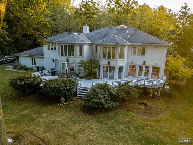 A remarkable retreat, architecturally captivating located only 6 miles from the GWB bridge. Set on park-like one acre property  in the Maugham school district f Tenafly, this beautiful modern bright home estate is a pleasure to see and live in.   Featuring approx. 6500 sq ft of living space (not incl basement) a separate unit zoned for office use with separate entrance.  A huge master suite extraordinary architectural detailing. All bedrooms are very generous, and the newer modern white eat in kitchen featuring all Miele appliances installed a few years back.  The grounds are totally private and away from the road featuring gorgeous plants and a fish pond. Complementing this beautiful home is an attached 3 car garage,a fully finished basement and 5 heating/cooling zones The best of indoor and outdoor living in this exceptional residence. A MOTIVATED SELLER!!TAXES REDUCED TO $36,008