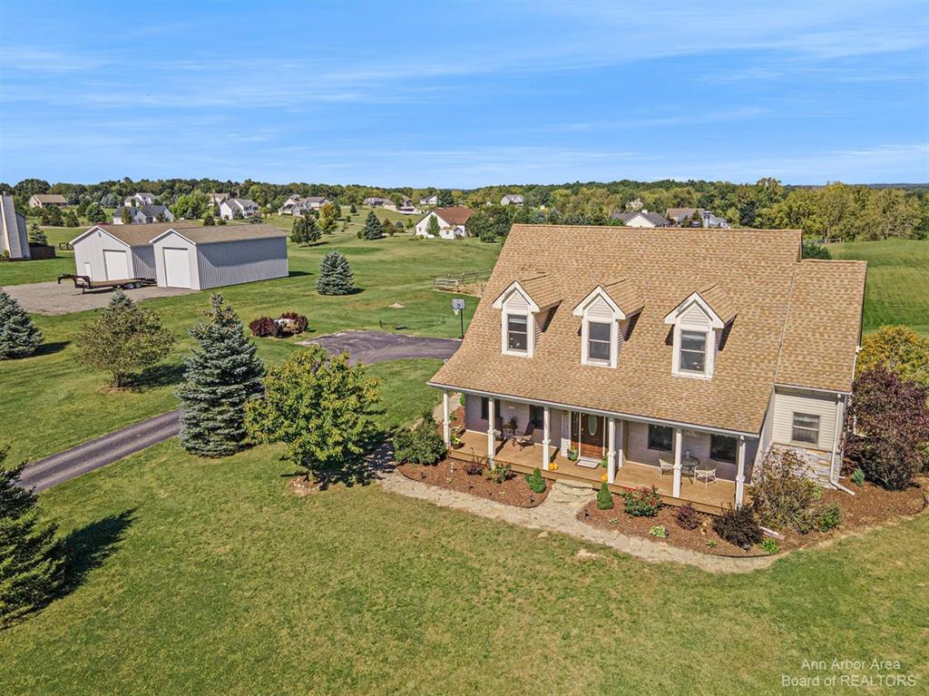 Custom built home with gorgeous, peaceful views from every window! This 4 bedroom, 3.5 bath cape cod features a desirable first floor primary bedroom, ensuite bathroom, double vanity, a jetted tub, shower and walk-in closet. The kitchen shines with a large island and tons of granite countertop space. Rounding out the main floor is a convenient laundry room off the 2 car garage, formal dining room with crown molding, half bath, cozy great room w/fireplace and a huge covered back deck. The second floor is home to 3 more bedrooms and 2 full baths (1 ensuite). The lower level is nicely finished with a bar area, wood stove, and a walk-out to a huge flag stone patio and garden area. It's also plumbed for a 4th full bath. This home has TONS of storage, a whole house fan and Pella double hung windows. Situated on nearly 4 acres, the lean-to is already in place for your horses or a hobby farm. Right outside of Manchester and only 30 minutes from both Ann Arbor and Jackson, this is country livin