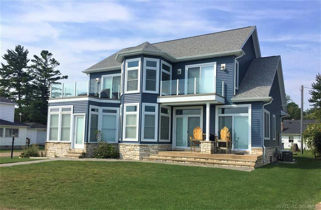 You will want nothing more after seeing this gorgeous lake view home with beach access! This home offers 3143 square feet of luxury living space. Fully appointed kitchen with stainless steel appliances. Beautiful hardwood flooring on the main level & lovely quartz countertops throughout. Four bedrooms, three with their own amazing view of Lake Huron & 3 full baths. There is also a 4 season sunroom, two glass-railing balconies off of the 2nd floor & a bonus room with a custom bar, beer fridge & wine cooler. These are just some of the amenities that you quickly realize you can't live without. Grab your beach toys from the over-sized attached 2 1/2 car garage and spend your day at the beach, capped off by a hot outdoor shower. Spend the evening sitting on the front porch gazing at the lake & stars or by the back yard firepit. Home features a high efficient furnace, spray foam insulation, central air, back up generator, & tankless water heater. Don't miss out on this amazing opportunity!