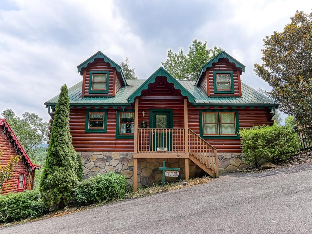 """Income producing 3 bed, 3 bath cabin in Gatlinburg with mountain views, a theater room and resort pool. Being sold fully furnished and turnkey ready. This ideal 5 star log cabin is perfectly located near The Great Smoky Mountains National Park and all the city of Gatlinburg has to offer. Nestled in Mountain Shadows Resort that offers outdoor swimming pool, playground and pavilion for owners and guest has low HOA fees, city water and sewer. Interior boasts a true cabin feel with wood covering floors to walls to ceiling! Main level features an open concept living room /kitchen/ dining area large enough for your entire party to sit comfortably with cathedral ceilings and a lovely stone gas fireplace and TV in living area. The fully equipped, spacious kitchen has brand new refrigerator, stove and microwave. Easily accessible utility closet with washer (replaced in 2021) and dryer. Tastefully decorated throughout with a mixture of log-cabin charm and modern amenities. The master suite is conveniently located on the main level and two bedrooms on lower level. All 3 bedrooms are private with their own private full bathroom with large closets, and their own French door to access the back decks to enjoy the peaceful woods setting. As you walk down the stairs to the lower level, to your left you'll be greeted with an impressive theater room with 65"""" screen TV (purchased 2020), surround sound and comfortable theater style seating and to your right a game area with foosball table for hours of entertainment. Outside on both levels of the covered decks enjoy sitting back in a rocking chair while you take in the fresh pine forest setting and the mountains view in the distance. Main level deck is ideal for entertaining with a 6 person hot tub, plenty of seating, and no-fuss grill area that is hooked up to the natural gas so no fear of running out of propane or being left with a charcoal mess. The curb appeal on this recently stained and painted log cabin topped with a green tin roo"""