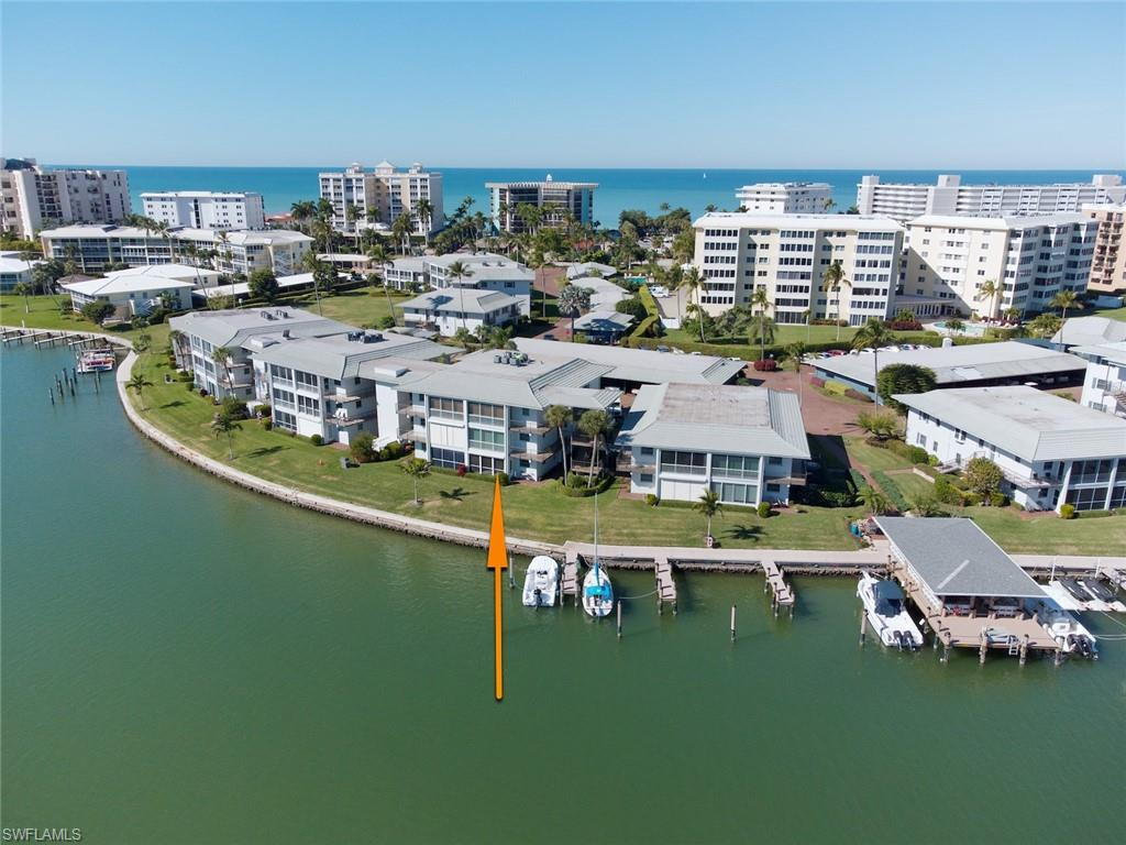 """WATERFRONT LIVING! The dream combination of BEACH & BOATING can be yours at this intimate tropical enclave. Cherished by its long-term owners as the place they celebrated many winter vacations, this impeccably maintained First Floor, End Unit residence offers an """"up close & personal"""" view of Outer Doctors Bay. Bring your kayak, paddleboard, boat… or just slip on your flip flops as the beach is directly across the street! The inviting, light-filled living space has a generous feel and offers excellent storage. You'll appreciate the energy efficiency & storm protection provided by impact windows and electric shutter on sliding doors. Situated in The Moorings, known for its gorgeous tree-lined streets, the complex features community boat slips (direct Gulf access with just 1 bridge). Take a leisurely stroll to The Village on Venetian Bay for dining or shopping and return home for a swim in the sparkling community pool. As the day winds down, join your newfound friends at the community Bayside Pavilion. This is what life in Naples is all about! All the details you value including new A/C in Jan 2021 + a covered carport & storage locker. NOTE: lease in place thru 4/1/21. VIEW THE VIDEO!"""