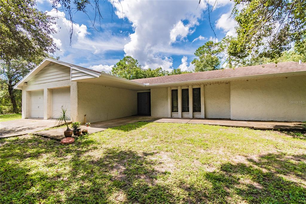 A unique property which features two driveways, with one directly off Gunn Hwy and the other on Cain Rd.  This has lots of potential and is an investors dream, to either be rezoned for a business/professional park, or update the current home, which is prime real estate sitting on a 2.2 acre lot, with much of it undeveloped!.  The home features 4 bedrooms, 2 baths, 1,814 sq.ft. with an oversized 2 car garage and a large screened lanai, surrounded by trees and a creek. Upon entering the home to your immediate right of the hallway is the large family room which leads on through to the dining area with sliders out to the lanai. From here to your right is the master bedroom which features a walk-in closet and en-suite with sink and tub with shower overhead and additionally has sliders out to the screened lanai. Back inside and past the dining area into the kitchen with lots of cabinetry, which connects through to the open and bright living room with additional sliders out to the 12x22 screened lanai, that offers plenty of space for entertaining and family gatherings. Adjacent to the living room is the fourth bedroom which could also be used as an office/den which has sliders out to the fenced side yard. Also from the living room is the hallway to the other secondary bedrooms and bathroom with sink and tub, that has access out to the backyard. This home does need some TLC to bring it back to it's former glory, but has a solid floor plan. It is ideally situated within a mile of FL 589 with quick access to the airport and downtown Tampa and is surrounded by grocery shops and restaurants. Gunn Hwy and Cain Rd have both benefited from recently repaved roads in the last few weeks. There are no HOA or deed restrictions. CASH ONLY SALE!