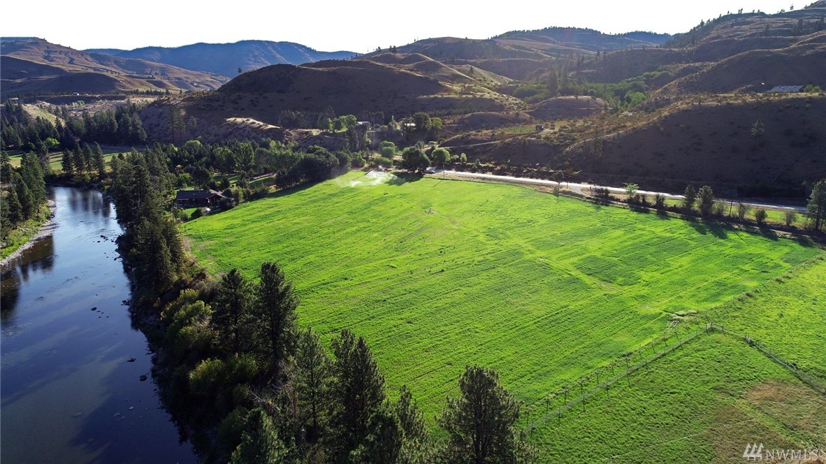 Bring your horses and house plans! Rare opportunity--10.5 irrigated acres w/Methow River frontage. Irrigation system in place, planted in alfalfa. Private 150 GPM irrigation well. Also perfect for other livestock, row crops & gardening. 600 feet of high bank river frontage 7 miles south of Twisp & 15 miles south of Winthrop. Easy access to the national forest & the restaurants, shops, music, art, & recreational opportunities of this great community. Mountain & river views for your country home.