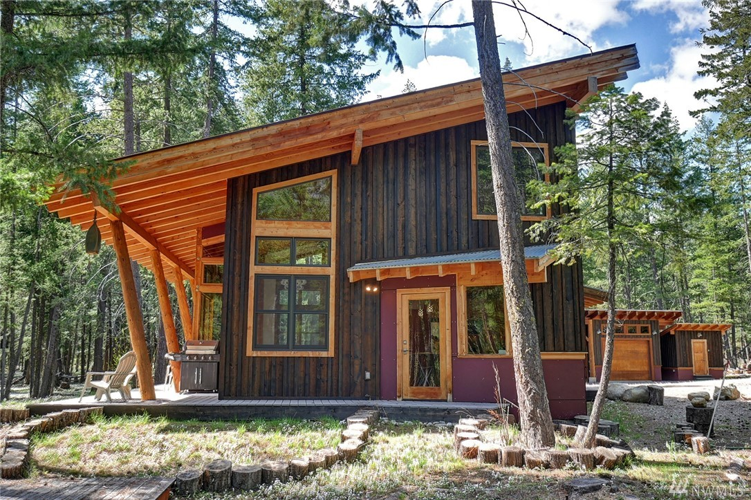 Contemporary Mazama home--the perfect Methow Valley style! Create a view of Goat Wall w/selective tree thinning. Bold lines & creative use of natural materials. Logs from the property milled for beams & flooring. Lots of glass in great room. Butcher block kitchen counters & walk-in pantry. Beautiful stairway w/custom railing--so many unique details. Two upper bedrooms w/wool carpets. Main floor room w/French doors for master bedroom or family room.The perfect 5-acre base camp for your Methow fun