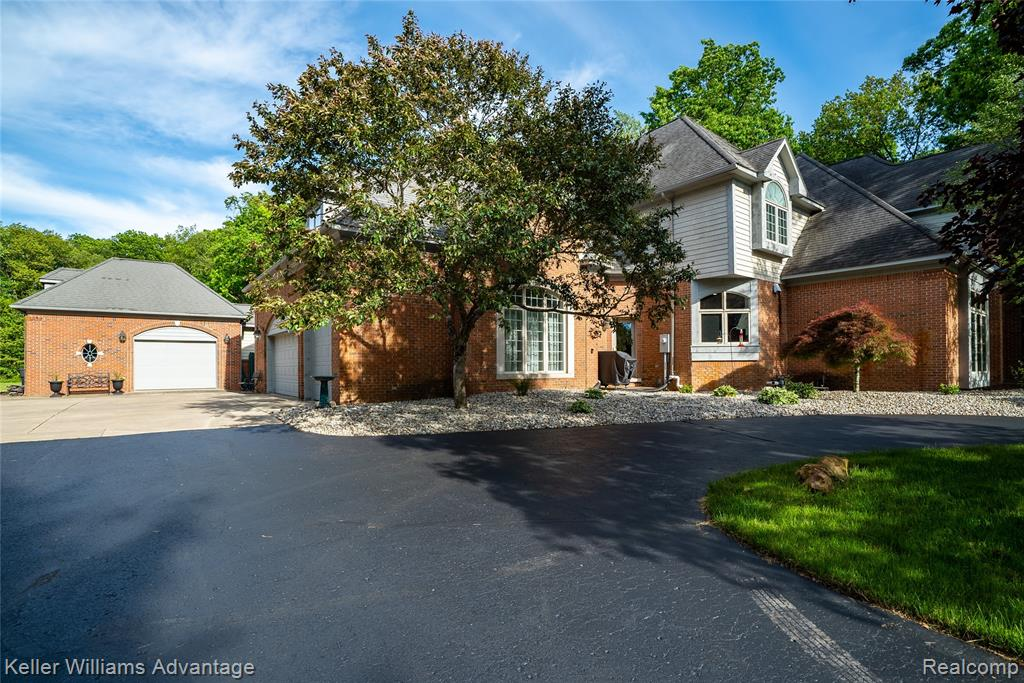 Stunning, 4 bed, 4 ½ bath, brick 2-story home in Hickory Ridge Farms, nestled on 3+ acres in highly sought after Milford w/award winning Huron Valley schools. Main floor features library w/built-in shelves, formal dining rm w/butlers pantry, living rm w/fireplace & floor to ceiling windows allowing ample natural light, laundry room w/doggie shower, crown molding & Coretec flooring. Kitchen w/Viking range & dishwasher, granite & wood countertops w/seating, SS app, eat-in area, flowing effortlessly to family rm. Main floor master w/walk-in closet, dressing rm & en suite w/jetted tub. 2 upstairs beds each w/walk-in closet & en suite. Mother-in-law suite boasts bedroom, en suite, kitchen, dining area, living rm, balcony & private entry. Professional landscaping, deck w/gazebo, fenced area, attached 3 car w/oversized bay for boat or RV, 1 car detached w/workshop. Zoned heat & A/C (2 units each), 1 of 2 HWH, '17. Metroparks, lakes, playgrounds, shopping & dining nearby. Must see! Won't last!