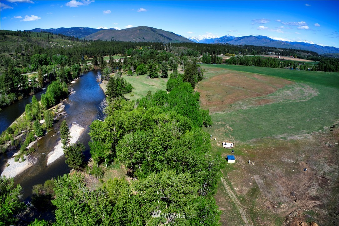 At last! Methow River front ready for your dream home! Level 4.65 acres. Private well, power, septic & propane on site. 2-RV hookups and camping platform await your summer adventures. Take your time to build and camp on your own land! A rare find! Amazing mountain views, sunshine and the sound of the river. What else could you ask for? Upper parcel out of flood plain. Bring your vision and your house plans. Riverfront parcel in conservation easement to protect the natural beauty. Short walk on the well worn path to your own sandy beach and picnic area. Idle the summer away fishing and playing in the water. Easy access to Winthrop and Twisp. All seasons trails just minutes away. Peace, privacy and nature. Start living your Methow Dream!