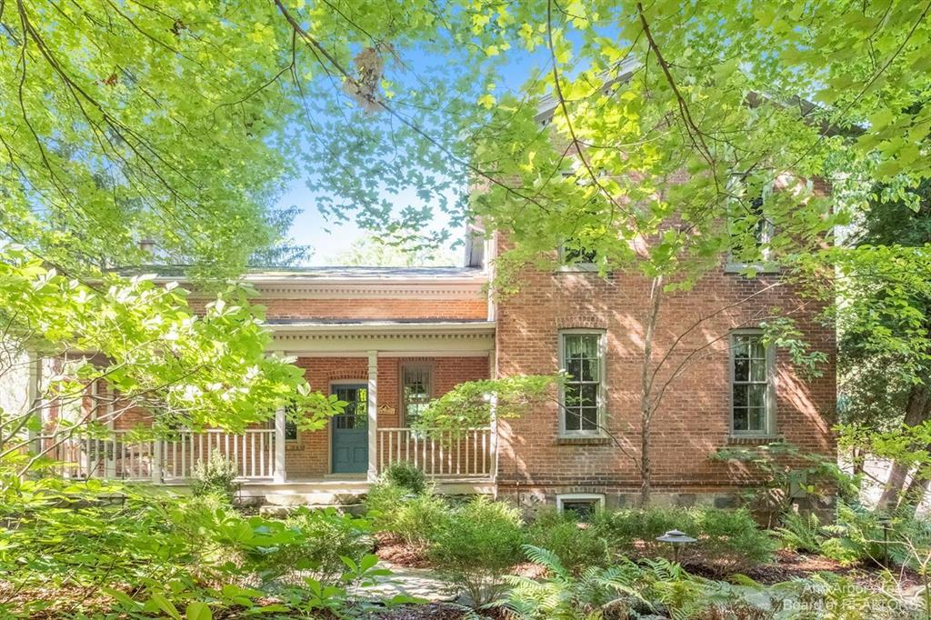 Classic brick farmhouse in a great NW Ann Arbor location set nicely on a 2.4 acre knoll. This special home has history & is loaded w/charm. Expanded and improved in 1995 to add open kitchen to great rm & 1st flr primary suite. Welcoming stone walkway & front porch set the mood as you enter. 1st flr offers spacious kitchen w/reclaimed wd floors, hickory cabs, island & plenty of rm to cook & entertain.  Kitchen open to great rm w/brick FP & blt-in bookcases & cabinets on each side. Formal dining area & nice powder room. 1st flr study (was parlor) has W/I closet (could be future laundry rm). 1st flr primary suite has W/I closet & French drs to backyard. Primary bath has travertine flr & shower. 2nd flr has 2 bdrms, study & 2nd full bath (3rd bdrm is adorable w/blt-in bunk beds). Stone basement has walk-out dr & laundry. Mechanicals incl GFA & gas boiler for HW heat, newer elec panel, newer HWH & well bladder. 3 car detached garage & paved area for parking. Garage was built w/2nd flr heate