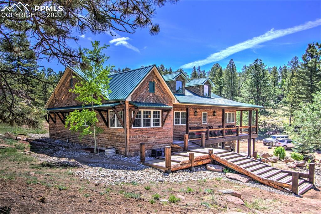"""Mountain rustic home located on 20 acres, with 7+ acres of horse pasture, and additional meadows through the property. Newly renovated with rough log siding, """"grand"""" entry staircase leading to the wraparound covered deck, composite decking. Rear covered arbor porch off the living area, outside entertaining has been the focus of these extravagant details! Ranch floor plan with in-floor radiant heat, newer boiler, and tile. Office/hearthroom off the entry, large formal dining room fit for Kings & Queens,"""