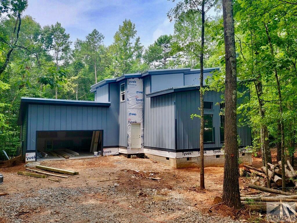 BEAUTIFUL NEW CONSTRUCTION- Located in the sought-after subdivision of Snapfinger Woods. Snapfinger Woods is known for its large wooded lots and contemporary/modern style homes. It is also located at the end of a peaceful cul-de-sac. This subdivision is tranquil, private and conveniently located close to the UGA Vet school, shopping, dining and 15min from downtown Athens! This modern home is one of the few that are available in the Athens area. Tucked away in a large wooded lot sets it apart from the others. This lot also gives you that mountain cabin feeling with wildlife sightings, you will almost forget you are so close to town. The home has a spacious open floor plan & quality finishings throughout. It has 10ft ceilings throughout the main level to add an extra open feeling. You're sure to love the two story living room with 18ft vaulted celling, oversize, commercial grade, custom made window, a granite hearth wood-burning fireplace (with a gas log option that the new owner can add later) & an elegant staircase to the second floor. There is an open kitchen, dining area, & great room that is ideal for entertaining along with a large back deck. The kitchen has craftsman style cabinets, an oversized large granite island/eating bar with pendant lighting, & large pantry. Additional feature on the main level are an office/bedroom with a full bath and a large laundry room. It also includes a mudroom bench nook that leads to the large oversized two car garage with extra work space. Enjoy hardwood floors throughout main areas. On the second level you will find vaulted ceilings in every bedroom. The vaulted ceiling master has 3 over sized windows to allow ample natural light & make you feel as though you are sleeping amongst the tree canopy. It includes a large walk-in closet, a large master bathroom with 5' tiled shower, an elegant stand alone garden tub, as well as a double vanity. The other two spare bedrooms are nicely sized, with one having a over-sized walk-in close