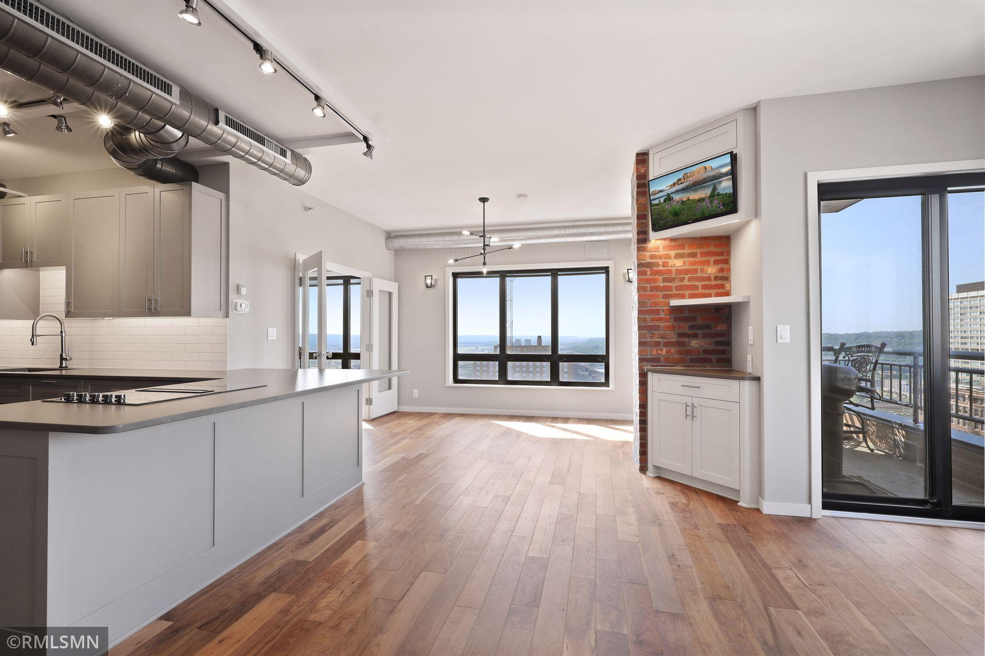 Enjoy panoramic views of the Mississippi River, downtown St. Paul, and the Capital from the luxury of this newly remodeled Lowertown 2 bedroom condo. From this 27th story industrial-themed unit you will be just steps from Mears & Rice Parks, CHS Field, Xcel Energy Center, Union Depot, the Farmers Market, light rail, and numerous bars and restaurants.   No expense was spared in remodeling this home! Custom cabinetry, designer lighting, and engineered hardwoods throughout. The open floor plan is great for entertaining, prepare meals from the kitchens' island cooktop, listen to music through the built-in Bose stereo system, and converse with friends while watching your favorite shows on the rotating TV on the classic brick column.