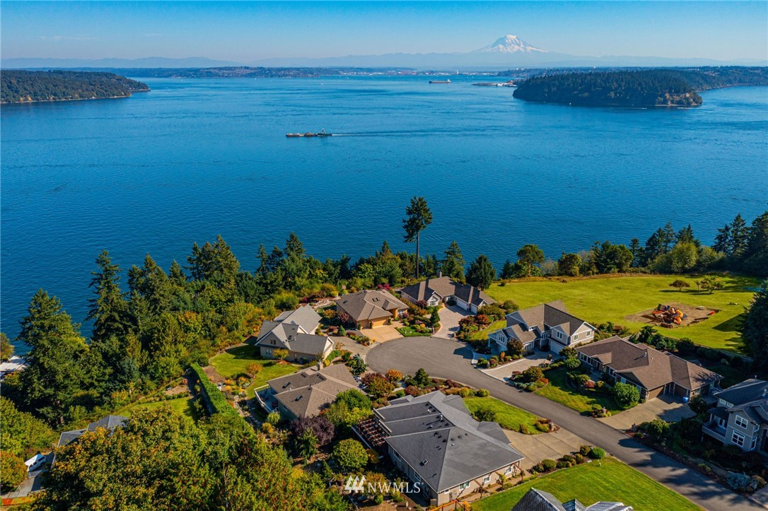 Location + View = It doesn't get any better than this! This custom built daylight rambler looks out over Colvos Passage & beyond. Mt. Rainier is larger than life, & the views of the sound, Vashon Island, Pt Defiance & the Tacoma City lights will mesmerize you! Tucked away near the end of this quiet, one street neighborhood in West Passage Ridge you will find this amazing retreat! Designed to perfection w/no expenses spared, you'll love this 4 bedrooms, 3 1/2 bath home boasting an open floor plan, two offices, hardwoods, granite, 9' ceilings upstairs, & 10' ceilings in the finished daylight basement! Enjoy relaxing on the deck overlooking the amazing view, while you enjoy the beautiful waterfall & mature landscaping. Home never felt so good!