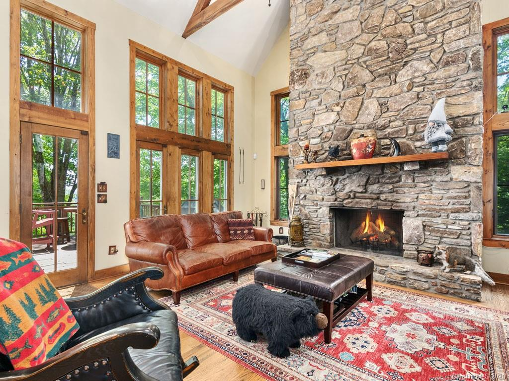Masterfully designed, this custom home has it all. The primary master bedroom is on the main level with a walk out to the expansive deck with views of the Cold Mountain. The master bathroom has a whirlpool tub, walk-in shower, and the walk-in closet of your dreams! Also, on the main level are hardwood floors throughout, a laundry room, a dream kitchen with granite counter-tops, gas cook-top, wall oven, and all of the other amenities within a well-designed kitchen that opens up to the two-story great room! The great room boasts a post and beam cathedral ceiling, dining area, plus a floor to ceiling wood burning stone fireplace. Once up on the upper level, the spacious loft area opens to the two-story great room. The upper level also has a second master suite with a locking walk-in closet, plus an en-suite bedroom. There is a fully finished basement level with another en-suite bedroom, an en-suite bonus room, and large family room with doors leading out to the fenced in back yard.