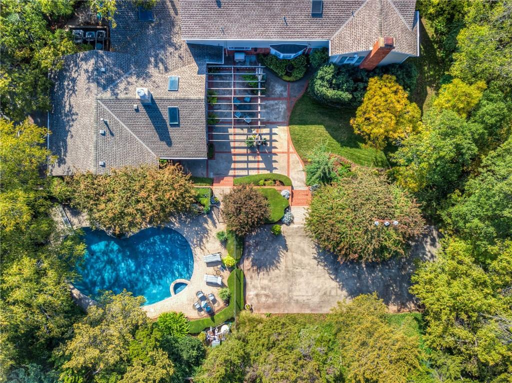 *PRICE IMPROVEMENT* Set back on a gorgeous .75 acre(mol) corner lot in the heart of Nichols Hills this stunning home has much to offer! You are welcomed by a circle drive and beautiful landscaping. Several large gathering spaces filled with natural light, warm wood floors and cozy fireplaces flow throughout the first floor of this classically designed home making it perfect for entertaining! The Kitchen, is centrally located with upgraded appliances, finishes, breakfast nook, and tons of storage. Also on the first floor: powder bath, office/bedroom, laundry room, & Guest Suite w/ private entry. The second floor is home to 2 Master Suites each with private baths and large closets, two additional guest bedrooms and full guest bath. Step outside and you are instantly transported to your own personal oasis with total privacy, lush gardens, pool with heated spa, and sports court! Don't forget the 3 car garage with extra parking! This home is truly a paradise indoors and out.