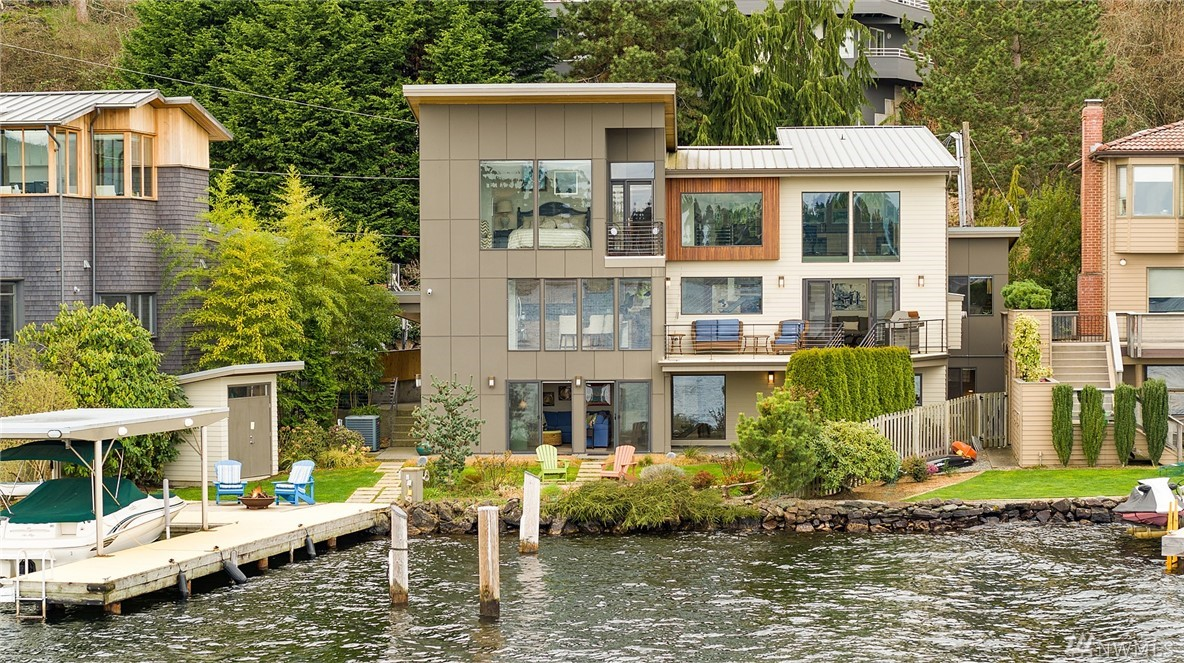 Spectacular NW contemporary w/63' of prime no-bank waterfront. Open floorplan boasts walls of windows maximizing breathtaking views of entire N end of Lk WA & Cascade Mts. Interior ftrs chef's kitchen w/island, floating steel staircase, upper level den/office & ground floor rec rm. Home blends indoor & outdoor living spaces w/covered patio, level lawn & entertaining pad at water's edge! Tremendous lake frontage w/deep water moorage, large dock, boat lift & rare covered boat slip in A+ location!