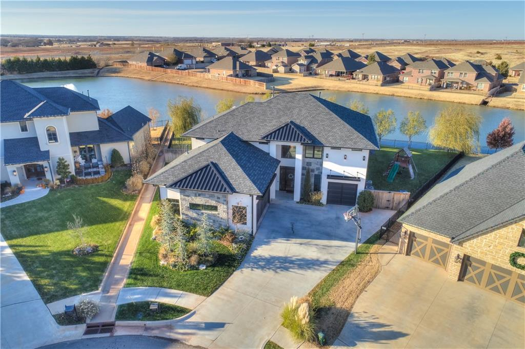 """""""Discover an elevated lifestyle within the walls of this contemporary home in the esteemed Rose Creek community. Styles collide with massive success; admire the delicate chandelier high above in the vaulted entry, sleek glass enclosing the wine storage under the stairs, & natural wood flooring stretching the length of the long hallways. The first impression for guests & neighbors alike will always be grand! Walking to the end of the foyer you'll find yourself in the living room that opens to a chef's kitchen loaded with all the bells-and-whistles. Ready to cook the perfect meal for the holidays? Host large groups easily. Parties will spill out onto the back porch to chat around the outdoor fireplace. When you're ready to relax from entertaining, retire to the master bedroom that keeps on giving. Take your choice of a long soak in the freestanding tub or a hot shower in the oversized walk-in. In addition, a home theatre, four more bedrooms w/baths & hidden room for play await you."""