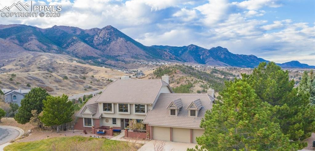 "Must see virtual tours! This spectacular home is for anyone who appreciates luxury and breath-taking views. This beautiful house featured on the ""Parade of Homes"" is a rare oversized 2.63-acre lot on the Northern West side of Colorado Springs. This luxurious ranch-style layout on a walkout lot spans 5,182 SqFt and features a massive 820 SqFt tri level deck, combine 6,002 SqFt of living, entertaining and relaxing areas with 4 bedrooms, 4 bathrooms, hardwood floors flow throughout the main level while towering two-story windows perfectly frame the panoramic views which highlight the Air Force Academy, Blodgett Peak and at night the Denver city lights will shine on the horizon. A gas fireplace warms the open concept living room, complete with a wet bar. You'll enjoy a formal dining room after cooking in the gourmet kitchen with granite countertops, high-end stainless-steel appliances, breakfast bar, and a spacious dining area. A pond with double water falls located just off the deck offers a wonderful ambience anytime of the day. Enjoy the main-level master suite, a large walk-in closet, private deck, and a five-point master bath with Jacuzzi. The upper-level loft features an office/media area. On the walkout level there is a guest master suite with a private bathroom and large walk-in closet. Family room features a gas fireplace, new wood floors. Two bedrooms located on the other side of the family room offer privacy with a shared full bathroom. Some extra features include lifetime warranty double pane windows, doors and concrete roofing. Backyard has over 400m solar lite, private hiking paths with handmade benches and a bridge nestled in nature. A short walk away, is the private Hunters Point community park for your family to enjoy; offering tennis courts, playground, picnic area, basketball court, & an annual HOA picnic. All this is peacefully set on a quiet cul-de-sac just minutes from I-25. Come tour this one-of-a-kind residence and experience it all for yourself!"