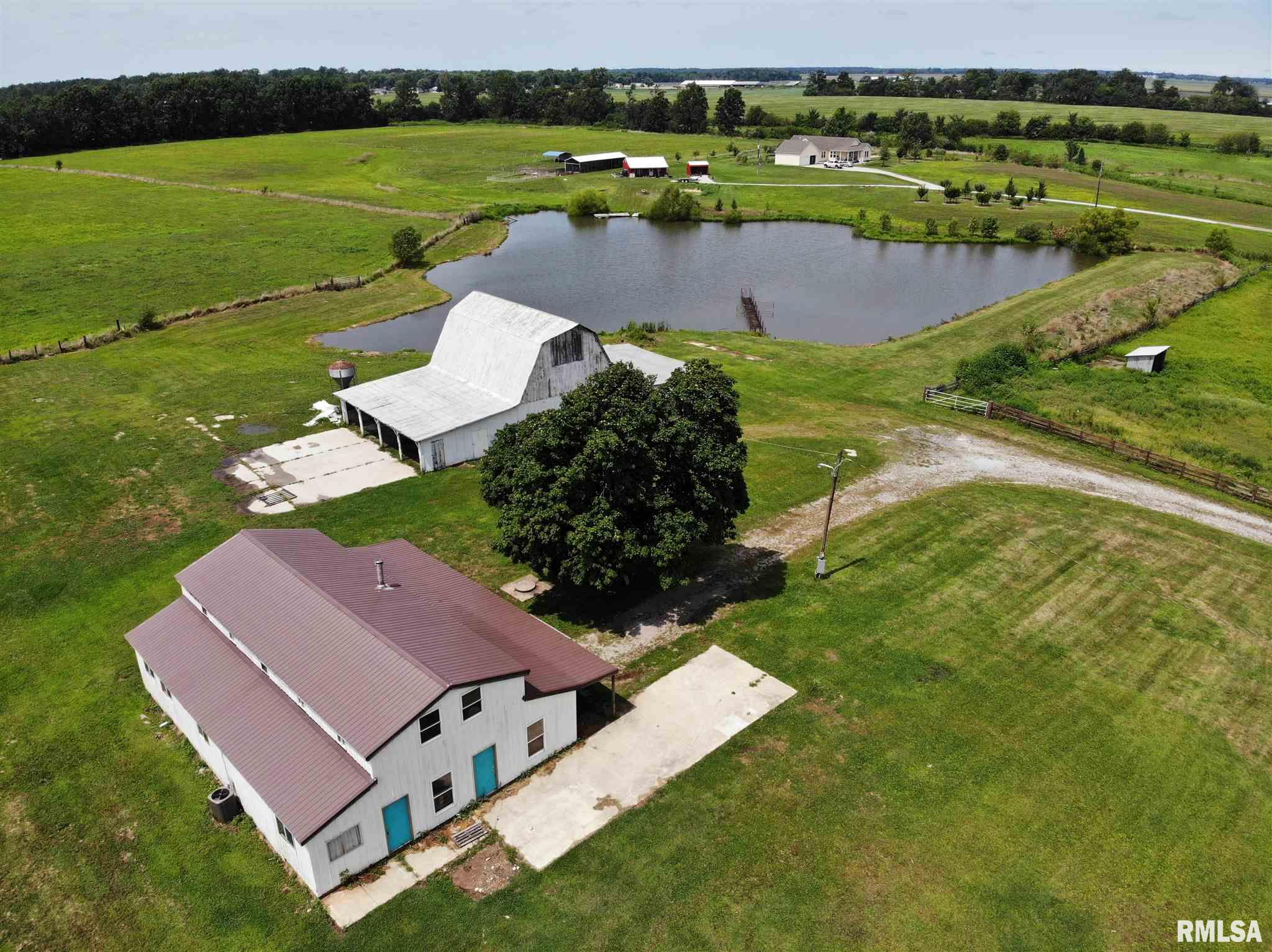 Looking for a few acres on the outside of town?  If you need a place immediately ready to accommodate farm animals this is it!  5 acres m/l, a story 1/2 pole building home with 3600 floor area, 1689 upstairs (2 bedrooms upstairs, 1 bedroom down).  This home has a new high efficiency furnace, new central a/c, new wiring and you can set this home up however you would like!  There is city water and propane gas.  The large wooden barn is unique as well!  The 36X24 barn has many wooden stalls, a large covered lean to, large hay storage area, lighting and new electric to it too.  To top it off, there is a large deep pond.  The property is fenced in the back.  There is also a portion fenced on the north side and it has its own lean to.  This property sets just outside city limits, so it is country living , but close to town.  Highly sought after property on N. Charleston Rd.