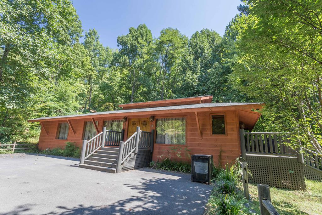 Come and enjoy the sweet life in this unique cabin in a park like setting just minutes to Gatlinburg and The Great Smoky Mountains National Park.  From the minute you walk in the door you feel like you are at a relaxing spa nestled in the woods.  Step into a large living room complete with fireplace, a pool table and large windows to let the outside in.  You will love the unique design of the stone floors thru out the home.    You or your guest are going to be taken back by the beautiful eat-in kitchen. Stainless Steel appliances. Open concept.   There are 4 king size suites, 2 with a private entrance.  Each bedroom has a private bath and unique stone lined shower.  The spa like feeling goes thru out the whole home.  Step out on the large deck.  A perfect place to entertain or relax in the large hot tub.  There is plenty of parking and even yard space.  This property would make a perfect place to call home, or second home.  It has been a successful overnight rental  cabin and comes furnished.  So many Special touches to make this  a unique property.  The rental history for 2021 is already  70,549. on the books.  Last August, 2020 till July of 2021 it has done $75,603. Some Drone photography used.