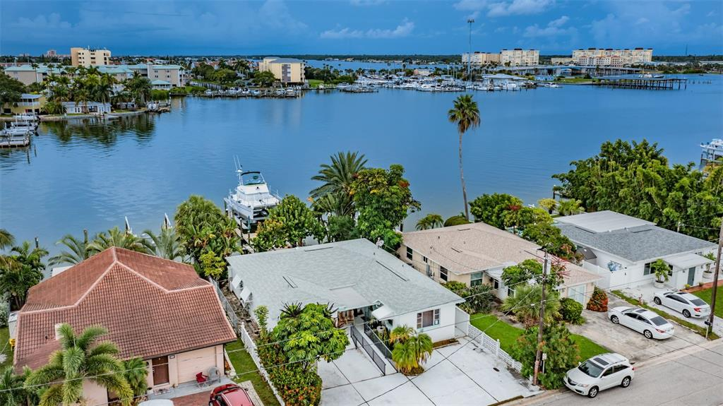 """Come view this Boat Lover's Oasis on Boca Ciega Bay in Madeira Beach! A quality 2017 Neptune 24,000 LB Boat Lift cradles a PDQ Passage Maker 32 Motor Vessel Catamaran that is available for sale separately! A 24 x 12 Dock was installed in 2019 and includes Plumbing and 110 and 220 Electrical. This spacious 3-bedroom, 3-bath home has 2 Master Suites with separate entrances (wheelchair accessible) for maximum flexibility. The open floor plan provides a view to the water from the moment you step inside. Living and Dining room have Hardwood floors and French doors to the back patio. The custom Kitchen boasts soft close wood cabinets with built-in shelving, stainless steel appliances, granite backsplash, wood countertops, ceramic cooktop, convection oven, vented range hood. Both spacious Master Bedrooms have an en-suite bath. Third bedroom has hardwood floors. Good size Utility Room. 2017 Hip Roof. 2021 Electrical Panel. 3-stage sprinkler system on reclaimed water. Home is raised up approx. 18"""". Located in the heart of Madeira Beach--close to shopping, restaurants and, of course, beautiful Madeira beach!"""