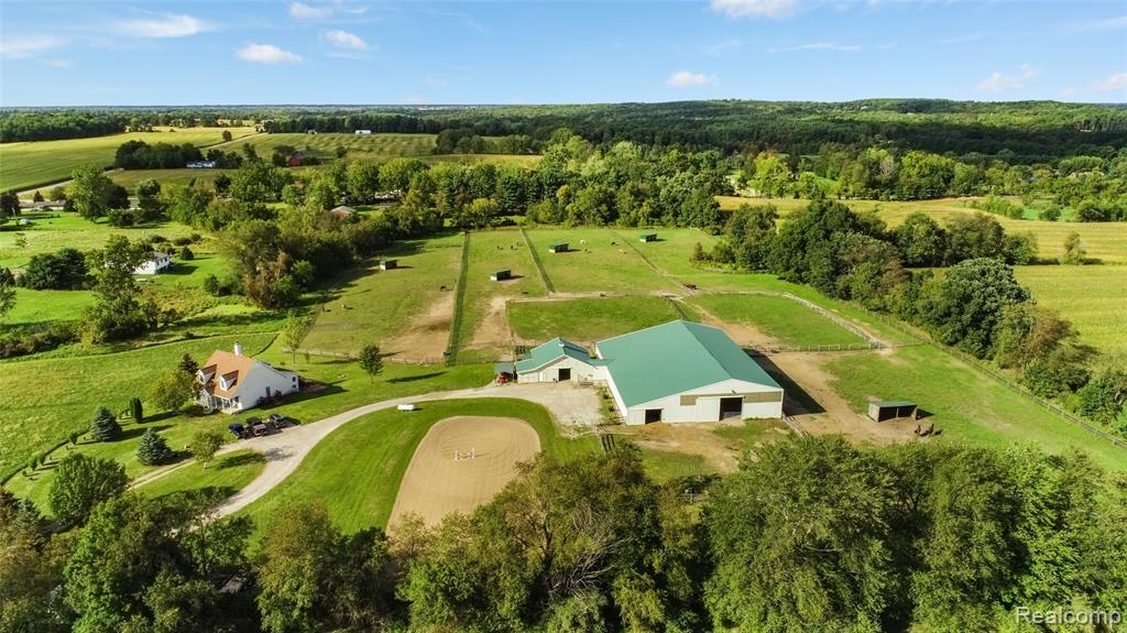 Marion Township equestrian facility on 18 acres! This home has a great layout and the perfect amount of space. With 3 bedrooms, 2 being master suites you have the option to be on the first floor or second level. This home features a very large open kitchen and eating area, a first floor office and a spacious family room w/ a gas fireplace. Second floor highlights include a third bedroom, loft area, and third full bath. An unfinished walkout basement provides plentiful storage and opportunity for more square footage if desired. Equestrian features include a 65'x120' indoor arena w/ new footing, 13- 10'x12' matted stalls, 2 grooming stalls and a large observation room w/ 12 tack lockers.  RAMM Flex and wood fence surround 3 run ins and provide plentiful pasture and turnout for the horses. Other exterior features include a 70'x150' outdoor arena, small pond and circle drive. Special use permit in place to allow boarding of up to 20 horses. Do not go to the property without an appointment.