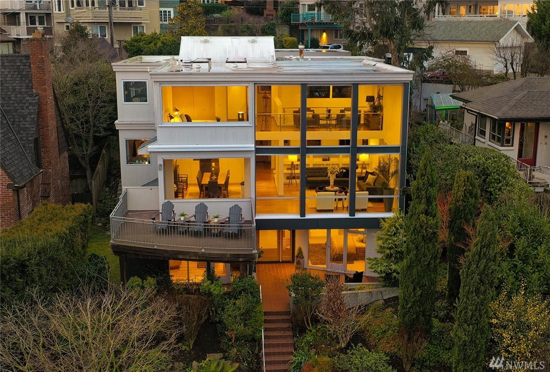 "This masterfully remodeled modern home is perched high above iconic Bigelow Ave N in QA & enjoys stellar views of Seattle Skyline, Mountains & Puget Sound. Modern floor-to-ceiling windows, new epicurean kitchen w/lux finishes, state-of-the-art cinema, solar heated swimming pool & bath house, lush mature landscaping, wine cellar, 3 car garage + 5 more off street, are captivating features of the aptly named ""Song House"". Commanding one of the largest lots in QA, the possibilities are endless!"