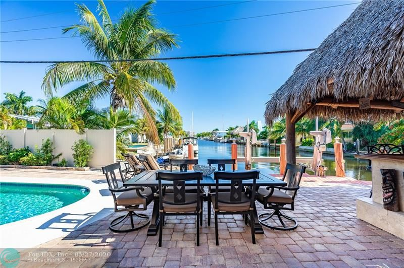 An amazing unobstructed view from your deep water, east facing dock is just the tip of the iceberg that this remodeled and pristine 4 bedroom / 3 bath home has to offer! 15-20 mins to the ocean by boat! Outside Tiki bar with power and water, 10,000 lb boat lift, in ground pool with spa, plenty of space to entertain and still have the grassy area for your dogs! Gorgeous chef's kitchen with gas range and all newer appliances, formal dining, and ample sized laundry room. Lovely bamboo floors in the bedrooms. All impact windows, doors and sliders, barrel tile roof new 2011 and flat new 2017. State of the art Carrier A/C 2016. You don't even need to paint to move in! Natural gas runs the dryer, stove, tankless water heater, and pool heater. Centrally located with easy access to the beach/shops
