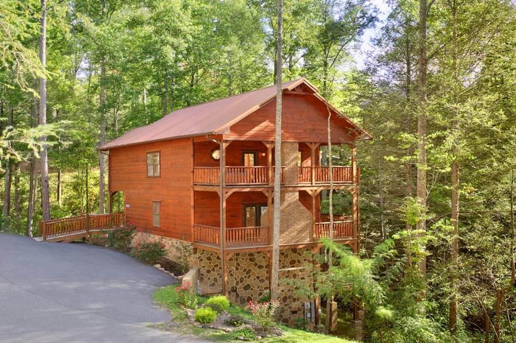 This spacious 4 Bedroom cabin features a stunning floor to ceiling outdoor masonry fireplace, wrap around decks, vaulted ceilings on the upper level, gorgeous stonework in the kitchen and a see through fireplace in the great room.  The fun does not stop with the impressive architectural detail.  The cabin also includes a game room featuring a pool table, oversize projector screen, and multi game arcade.  All of this in a serene wooded location just minutes away from the attractions of Gatlinburg and Pigeon Forge.  Contact us to inquire about the impressive rental history.