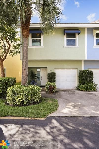 """Come home to this beautiful, well maintained & spacious townhouse in a gated community just south of Wilton Manors in the heart of everything. Huge master suite upstairs along with 2 additional bedrooms & bath + washer/dryer in hallway. Great Juliet balcony & sliders in master allow for lovely breezes & view of tropical patio below. Bright kitchen opens to spacious family room downstairs. In addition to the attached one-car garage with room for a second car in driveway outside it, this unit comes with a second one-car garage in a separate building. Parking for 3 cars! This excellent small community of townhomes has a great pool overlooking the south fork of the Middle River and is walking distance to absolutely everything """"the Drive"""" has to offer in terms of dining, nightlife and shopping."""