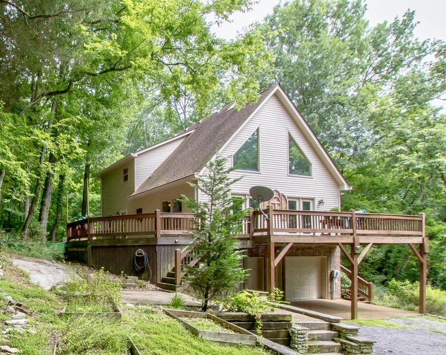 Whimsical Artist's Retreat on 9.3 ACRES in Franklin. Private, surrounded by mature trees & massive wrap-around deck, open & airy floor plan ft. hardwoods, oversized windows, stacked stone fireplace, soaring vaulted ceilings, loft-style primary bedroom w/ soaking tub, double vanities & closets. Walkout basement w/ private entrance, kitchenette & full bathroom- perfect AirBnB or in-law suite, 2 car garage w/ additional parking area — all conveniently located minutes to town.