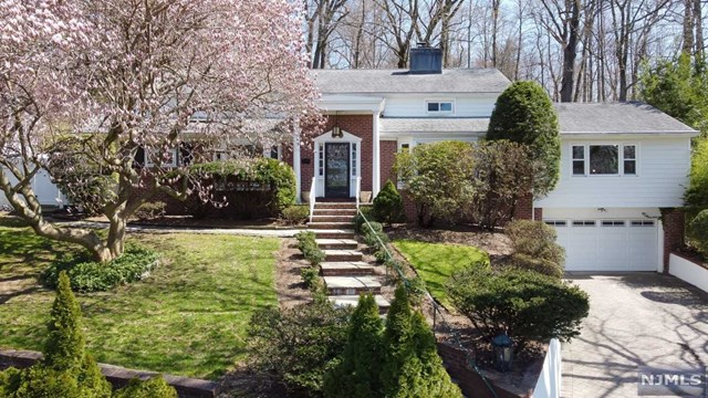 ALL OFFERS DUE MONDAY 4/12 BY 5PM! Situated on the top of Tenafly's East Hill close to the magical Nature Center! A perfect & desirable location. This 4 bedroom 2.5 bath home is just waiting for the next family to fill it with memories. Living room with a gorgeous brick wall and wood burning fireplace flows to a family room with impressive glass doors overlooking this private and lush property plus an updated modern kitchen and a dining room, ideal floor plan for everyday living. Tons of natural light bathe this home and the views of the manicured gardens are simply amazing. Primary bedroom with loft office space & updated bath, plus 3 additional bedrooms and full bath on the 2nd and 3rd floors.  Rec room, laundry room storage on the lower level offers many options for how we live today.  This home won't last!