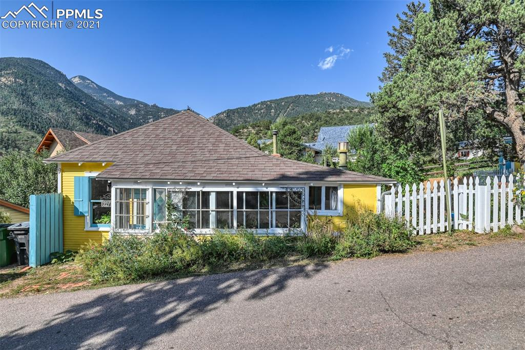 """HERE'S YOUR CHANCE! OWN A UNIQUE PROPERTY IN THE MOUNTAINS THAT'S ALSO CLOSE TO TOWN! Cute cottage built in 1899 on the hillside of Manitou Springs, larger lot than most as seen in drone photos. Lovely outdoor garden with a fireplace. Inside is a 2 bed (non-conforming), 1 bath with many vintage touches, hardwoods and space saving built-ins throughout. Homeowner loves the """"Historic character in this Victorian dollhouse in a charming mountain town. Breathtaking views of 10,000'+ high mountains right out the door!"""" Rainbow Falls, Incline, trails within minutes."""
