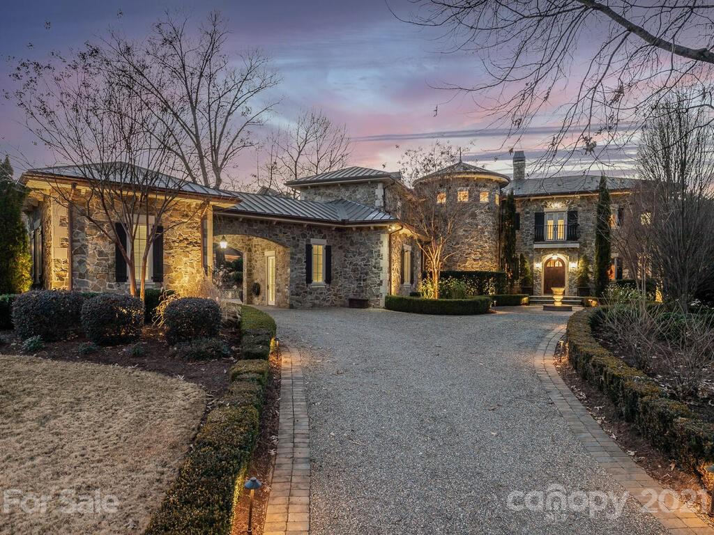 Tuscan Estate rests high above the shoreline embracing Lake Norman views. Sun kissed natural stone & warm copper roof blend old world & casual elegance. Soaring three levels overlooks deep water w/expansive views capturing all the colors of Lake Norman sunsets. Interior is warm & welcoming w/wide wood plank flooring and stone flooring creating relaxed refinement through out. Chef's kitchen w/two islands, custom copper hood, wood beams & high end appliances is open to breakfast area & wood paneled family room. Butlers pantry off kitchen-open to Living Room & Dining Room w/brick groin vault custom ceiling. Owners suite captures extensive waterfront views, spa bathroom, custom closet w/private covered balcony. Three bedroom suites w/private baths & laundry room round out upper level. Lower level: Wine Vault, Theatre, Bedroom suite, Office, Family &  Recreation Room w/entertainment bar. Waterfront Pool-Spa, covered porches, patio's & boat dock offer year round outdoor oasis on Lake Norman.