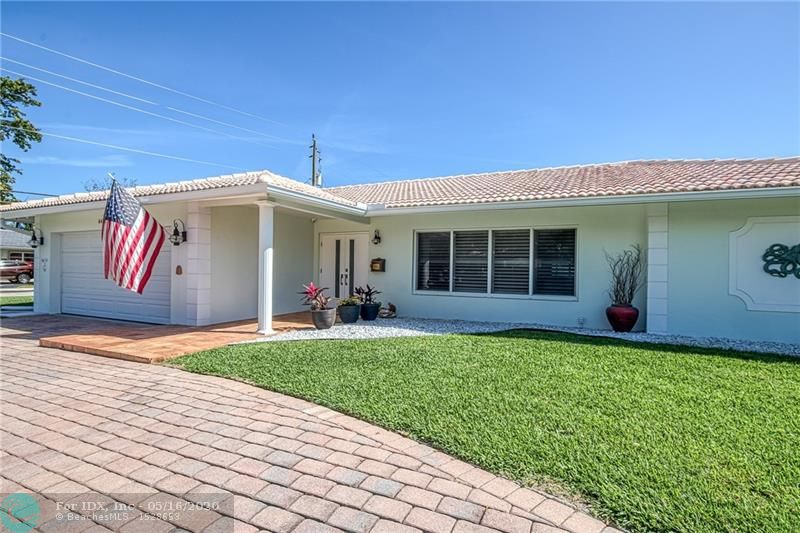 """OVER A ¼ OF AN ACRE! UPDATED & METICULOUSLY MAINTAINED 3 BEDROOM 2 BATH DEEP WATER POOL HOME LOCATED IN LIGHTHOUSE POINT JUST OFF THE NORTH GRAND CANAL. A CORNER LOT WITH 11,000+ sq ft , STEPS AWAY FROM DAN WITT PARK COMPLEX & A SHORT BOAT RIDE TO HILLSBORO INLET. VERY DESIRABLE SPLIT FLOOR PLAN W/ 18"""" TILE THROUGHOUT AND A VERY LARGE FLORIDA ROOM WITH SPECTACULAR VIEWS OF THE POOL, PATIO, DOCK AND WATERWAY. THE PROPERTY ALSO BOASTS A LARGE KITCHEN WITH MAPLE CABINETS, GRANITE COUNTER TOPS AND STAINLESS APPLIANCES. UPGRADES INCLUDE: NEW IMPACT FRONT DOORS, FULL HOUSE AQUASANA WATER FILTRATION SYSTEM, NEW POOL TILE, COPING & DIAMOND BRITE FINISH, SEAWALL HAS BEEN SEALED & RESURFACED, NEW DOCK INSTALLED WITH TANDECK MARINE DOCKBOARD, SALT WATER POOL, PAVER DRIVEWAY, ETC! A MUST SEE!"""