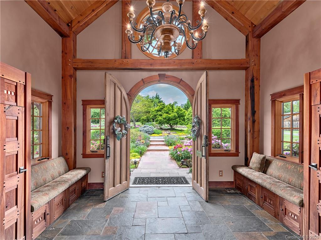 Rare opportunity to own a beautiful 33-acre country estate minutes from Asheville. This exquisitely designed, post & beam timber frame home boasts almost 6000 sqft, breathtaking mountain views, & river frontage. Enjoy soaring ceilings, 4 stone fireplaces, & an expansive terrace. The gorgeous kitchen is a chef's dream w/all the luxury features. Watch a movie in the state-of-the art home theater, enjoy a beverage poolside, or go for a swim in the natural rock, solar-heated swimming pool w/ waterfall & beach entry. Pick apples in the orchard, go for a walk in the countryside or fly fish the hatchery-supported trout stream. Property includes a workshop, commercial grade internet, Tesla supercharger, & solar energy. Guests will love staying in the log cabin or apartment. If you want horses or farm animals, you'll appreciate the flat acreage, with 7 fenced pastures, a charming barn, & regulation-sized riding arena. Minutes from Chimney Rock, Blue Ridge Parkway, TIEC, Biltmore Estate & more.