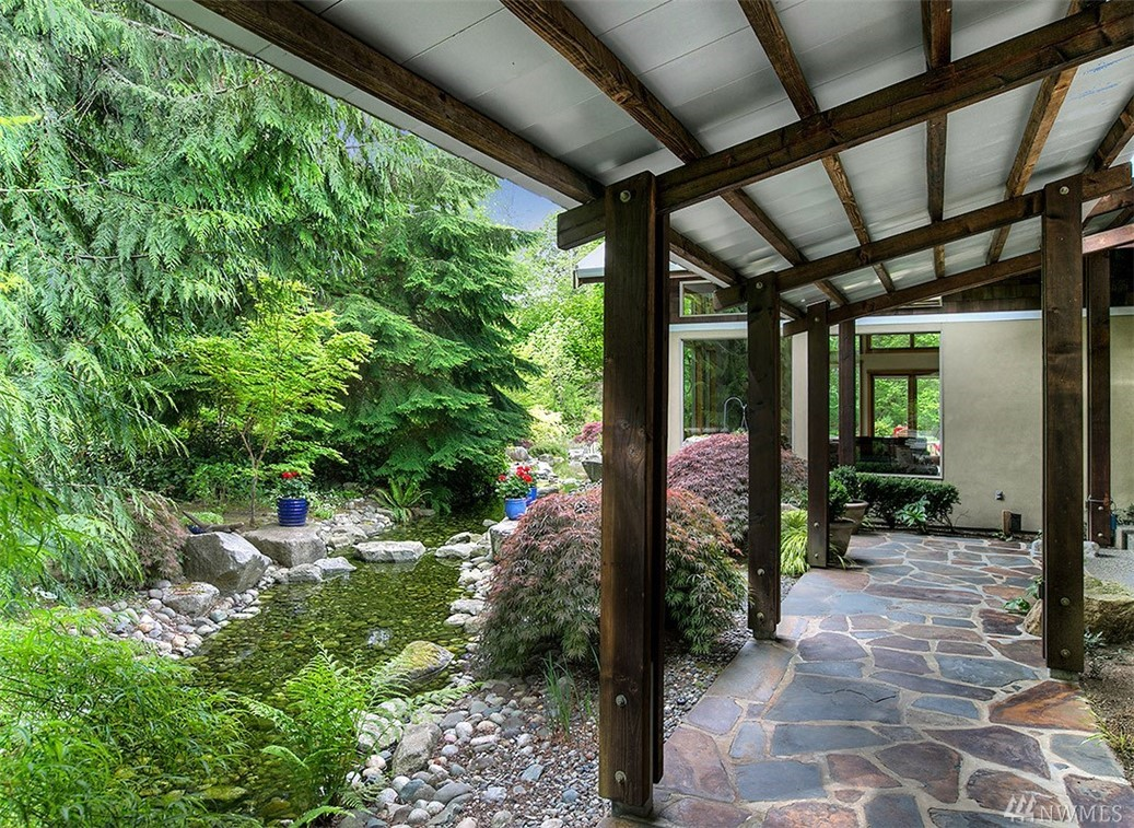 Your NW Contemporary private oasis awaits. Enjoy this gated paradise on 2.7 flat and sunny acres. Flowing water feature leads to a custom built home with spectacular great room. Main house is one level living + loft. Commercial appliances, radiant heat flooring w/newer boiler, metal roof, real stucco and Tesla charger. Full 1 bed apt above garage w/6 covered parking spots. Low maintenance perennial garden, fruit trees & raised beds. Top rated Lake WA schools. Pre-inspected. Watch the video!