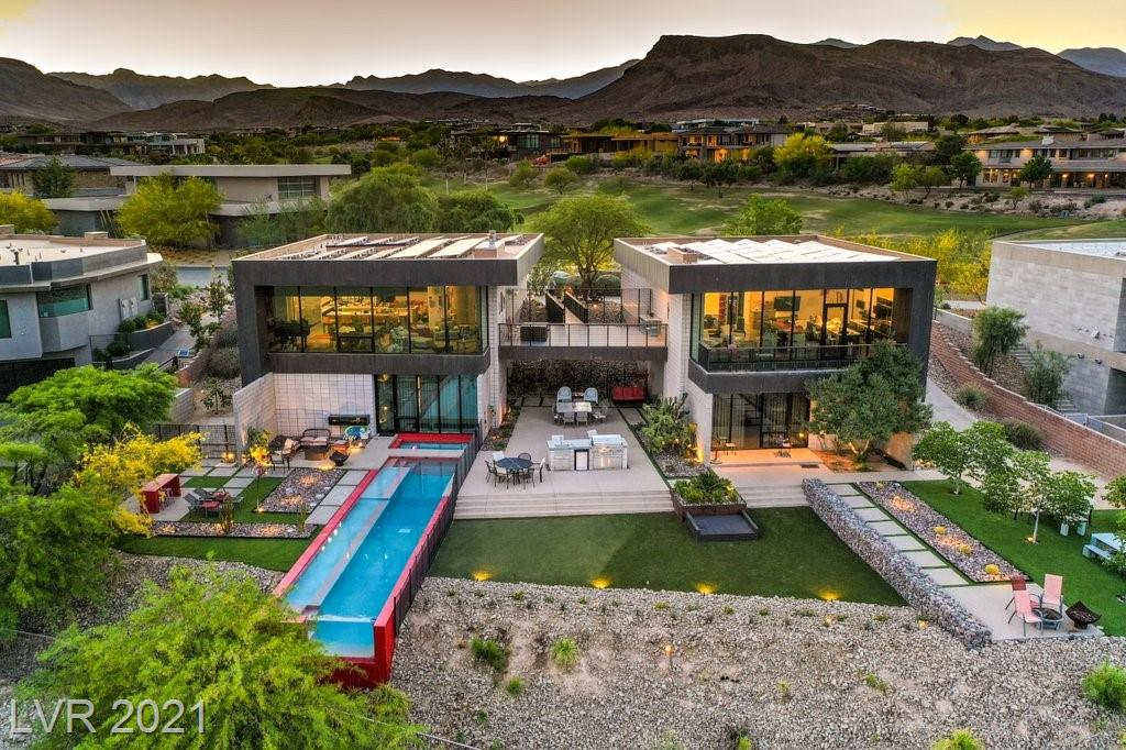Renowned Architect Eric Strain created this stunning, unique design.6 bedroom with media room,6.5 baths,floor to ceiling windows, solar panels,stunning lap-pool, large backyard designed for the stars, a breathtaking unobstructed view of the strip and Golf Course.The unique architectural design allows the space to be divided into two completely separate living spaces with a shared outdoor area. The house was built on two separate foundations using honed concrete block and load bearing masonry technique. Includes 2 kitchens, living rooms and laundry rooms. Excellent noise insulation providing privacy  between the two houses.  The house is ultra contemporary and modern, with an exterior featuring magnificent copper. It showcases the latest green technology and upscale finishes - Italian cabinets. One of the best lots and views in the Ridges. Cul-de-sac.Over 1/2 acre suitable for large parties. Must view! Access to The Ridges club included in the HOA fees. Gym classes, pool, tennis.
