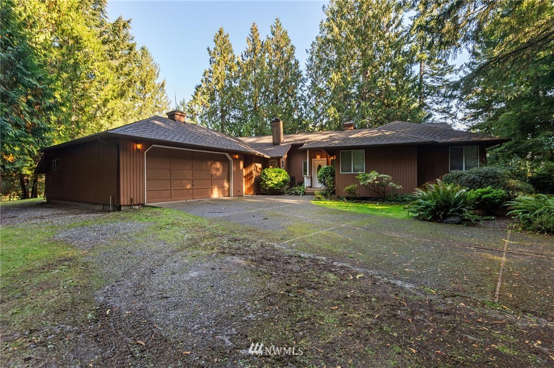 Nestled in the woods just off Olympic View, perfectly situated on 2.47 acres is a sprawling, private, single story home w/huge shop waiting for you! Wrapping deck, ample parking, outbuildings & garden area are just a few of the endless features. Gleaming hardwoods welcome you to the living rm & guide you into the light & bright kitchen w/custom cabinetry, corian counters, breakfast bar, dining area & family rm w/vaulted ceiling & skylights. 3 bdrms, den, 2.5bth & $5000 flooring credit!