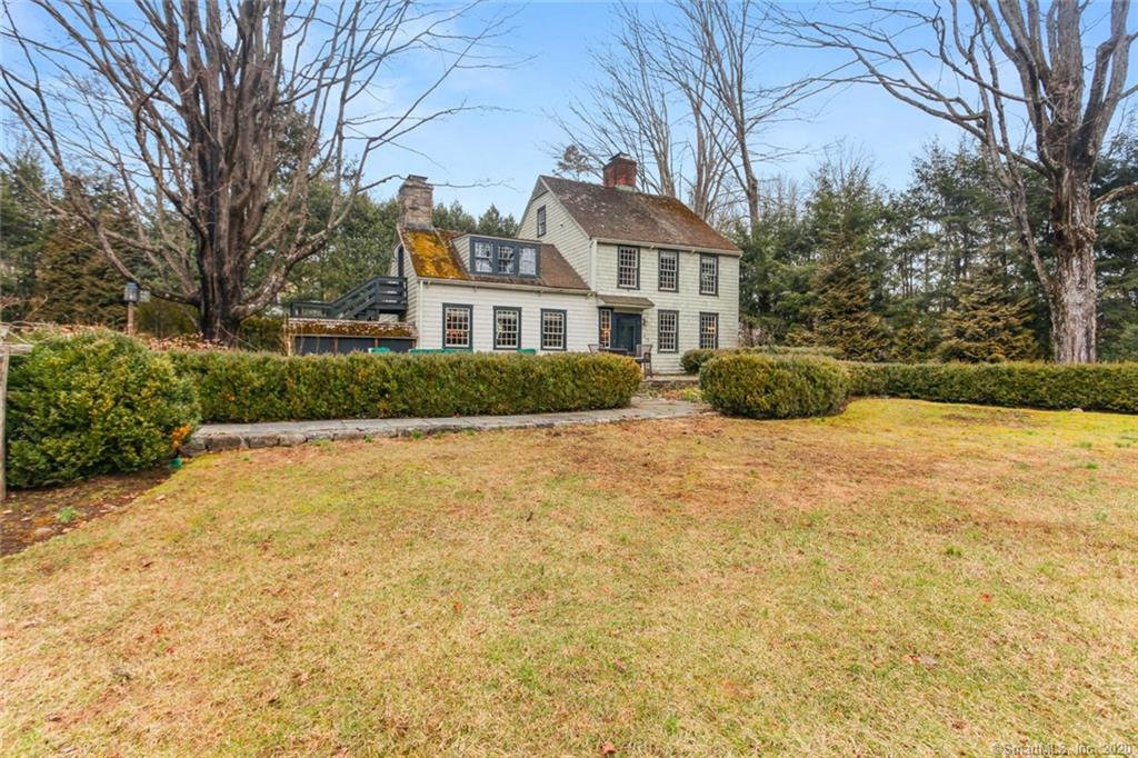 """Own a piece of Fairfield history! Tucked behind large arbors on one of Fairfield's most prestigious streets is a 1725-built home & a barn with 2nd floor apartment. Inside, wide plank floorboards, beams, exposed brick & open spaces grace the home & elicit charm, character & the enchantment only an antique home can bring. The fireplace in the cozy, front-to-back living/dining room puts the """"heart"""" in """"hearth"""" & sets the tone for the rest of the home. The eat-in kitchen blends a modern & historic feel with SS appliances and country style cabinetry. Finishing off the first floor is the family room & powder room. Upstairs, the master bedroom with beams, a huge walk-in closet & master bathroom with soaking tub and walk-in shower will charm you. The 2nd bedroom & full bathroom can also be found on this floor; the 3rd bedroom awaits on the 3rd floor. The detached barn is ideal for a garage with a studio apt above. Multifunctional, it can be used as an au pair suite, in-law apartment, guest house, artist's studio, or home office. Enjoy peaceful nights relaxing on your expansive lawn, playing fetch with the dog & watching wildlife on your two private acres with stunning foliage such as a yellow magnolia tree & a Weeping Katsura tree. This home offers the privacy of Greenfield Hill & is just minutes to downtown Fairfield, shops, schools, restaurants, highways, the train station & more. Enjoy country living in a one-of-a-kind home with rich history & love behind it."""