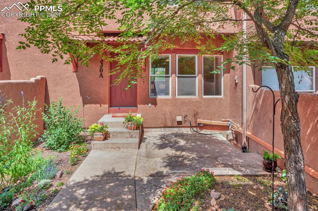 Feel like you're on vacation year-round in this darling, nearly maintenance free, townhouse in historic Manitou Springs! Upon entering the garden gate, take in the serene bloom-filled courtyard as you approach the front door of this adobe style unit. Once you open the front door you'll immediately feel the cool central air and notice the gorgeous hardwood floors, cozy Santa Fe fireplace and ambient lighting.  Well appointed kitchen with stainless steel appliances, granite countertops, beautiful high-end copper sink and breakfast bar overlooking the the dining area with walkout to charming deck with lovely views. The upper level features two luxurious bedroom suites, while the lower level boasts a 2 car attached garage. This unit also features curb side parking in front of the unit, which in Manitou is a rarity! Taos Village is a small, quiet community with a club house, swimming pool and lovely views of Garden of the Gods, rock formations and the mountains. Walk to some of the best restaurants and activities Manitou has to offer. Or perhaps, bicycle through the Garden of the Gods, take a quick jaunt to the mountains, Old Colorado City or downtown Colorado Springs!