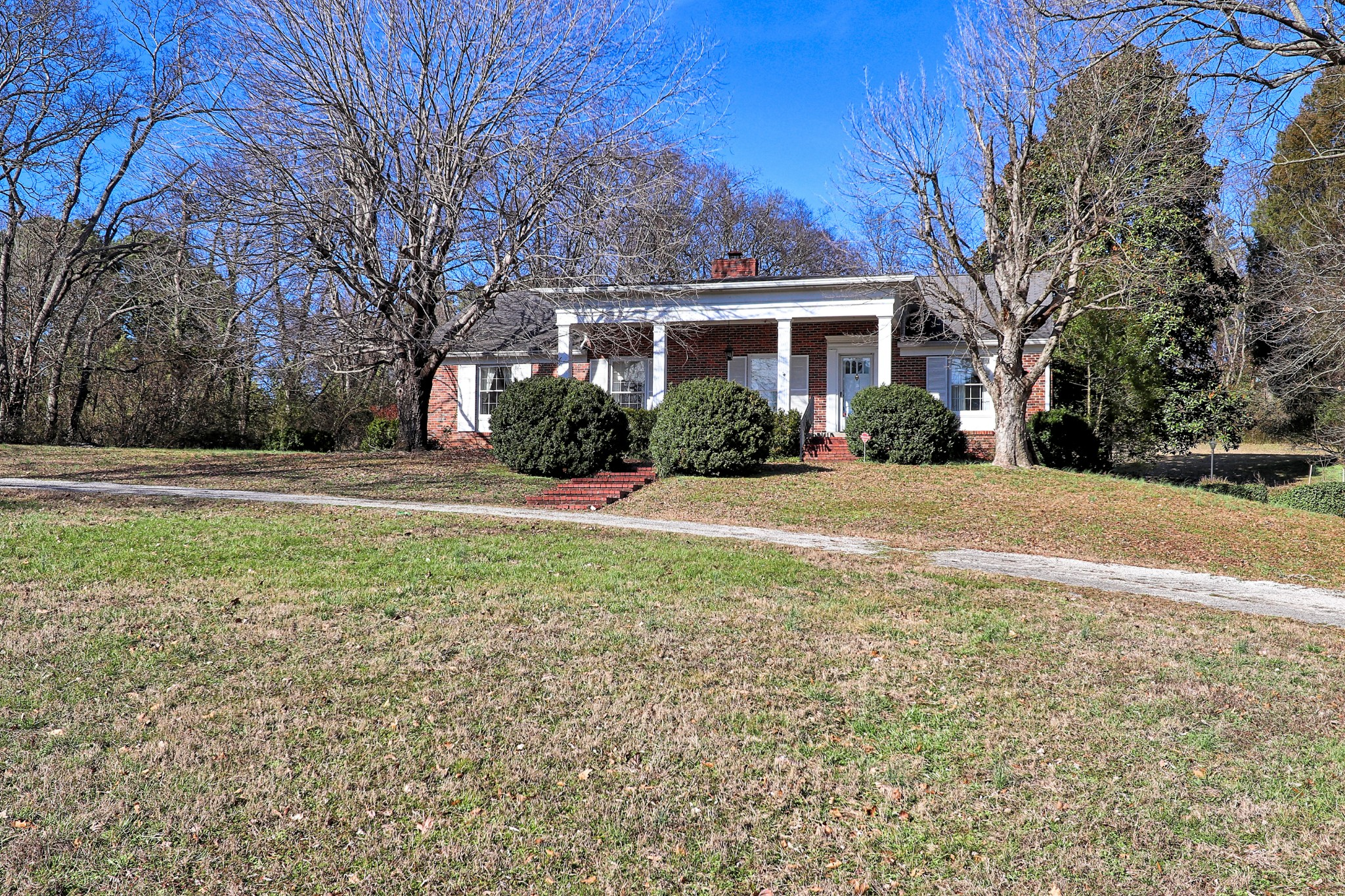 Classic, well-maintained home on 2.2 acres. 2 large dens + renovated basement. Neutral paint colors, spacious rooms, timeless fixtures & oversized front & back yard perfect for the person who wants to live in town & still have their space!  Back patio and front porches perfect for warmer weather on the way! Newer HVAC & renovated basement w/separate entrance.
