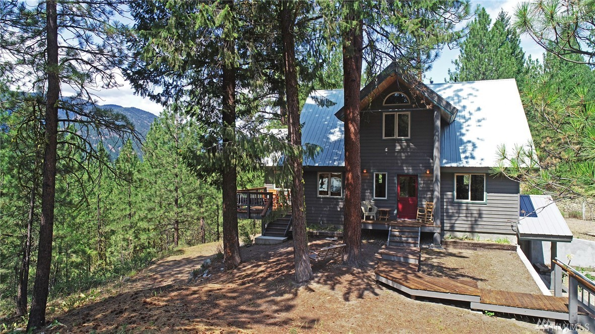 Creative mountain home w views of Mount Gardner & dramatic rock walls of Lucky Jim Bluff. Close to Mazama & trails. Sociable open floor plan w chefs kitchen, lg windows & sunlight. Interior connects w several decks that take advantage of different views & seasonal changes. Spacious ensuite master bedroom w walk in closet, tiled bathrm & sitting area. Media/rec room w sunroom/gym. 3 bdrms/3 baths. Two practical mudrooms. Attached garage/shop space plus dbl garage w insulated studio space above.