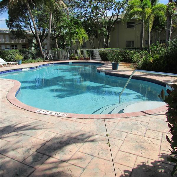 Just a short walk to Wilton Drive, shops, restaurants, super market, coffee shop, clubs. This Unit is   conveniently located near the pool and featuring a galley style kitchen, Dining area just off the kitchen, all tile floors and one of the few units in this complex with an in unit washer and dryer. This unit comes with 2 parking spots. Presently occupied with a tenant, lease ends June 30, 2021. Investors can rent immediately.