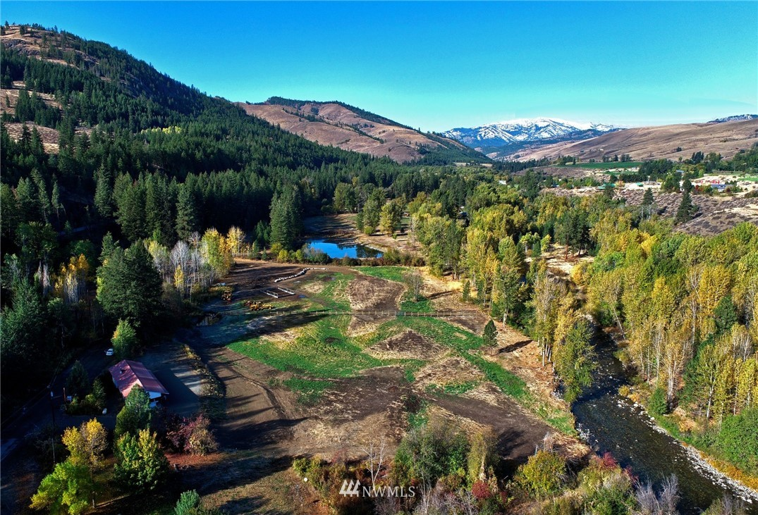 Rare Twisp River 3.7 Acres!Beauteous 350+/- ft low-bank waterfront to enjoy!Level,partially fenced.Established Well,on-site septic system,new plumbing.Reynolds peak, 3AM Mtn views.Move-in ready,restored 2 Bed,1 Bath, single-wide,great storage, owner use / rent. Engineered truss metal roof over building.Large wood deck. Spacious carport.Appliances included.Wood stove.Updated interior.Create farm,equestrian trails,garden & more.Enter on-grade to daylight basement garage of new home footprint. Seller may consider removing MH & Shed roof building.