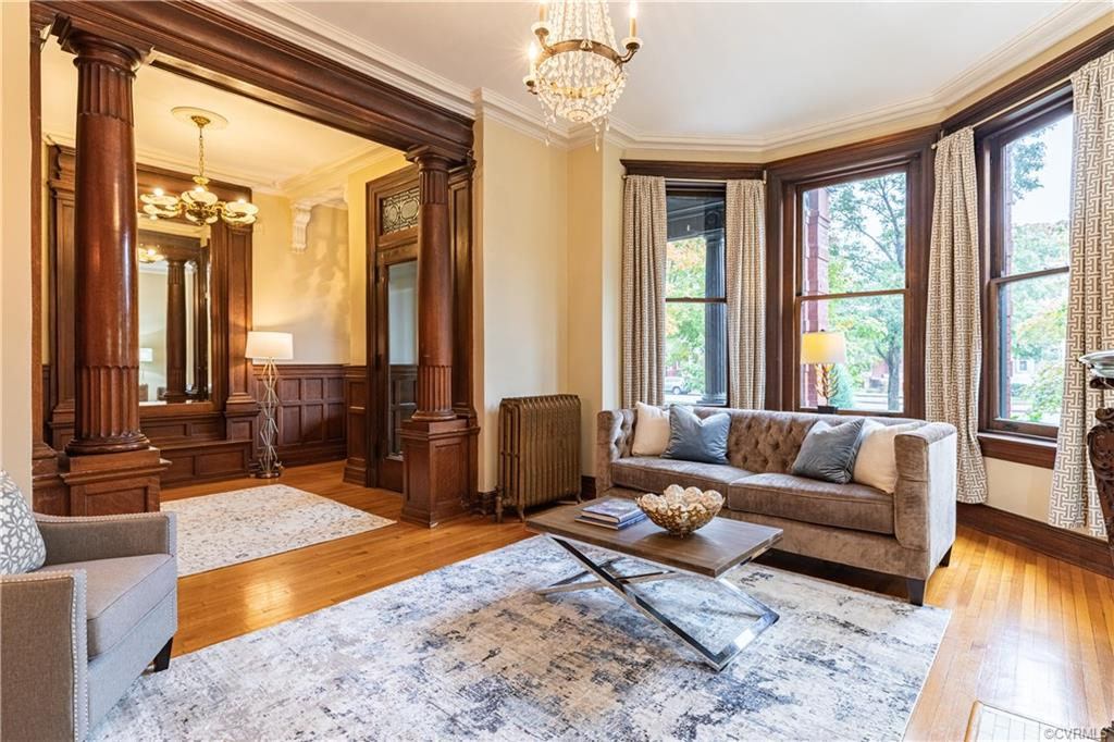 Classic meets renovated in this 1906 Italianate Renaissance stunner. The entryway wows with original leaded glass windows, built-in benches, stained paneling, wainscoting, and heart pine floors. The sprawling main floor includes a living room, dining room, sitting room, all with original fireplaces, working pocket doors, lots of natural light through enormous windows, and bespoke paneling. Then there is the kitchen which retains its early 20th-century charm with original hutches, even though it has been renovated with professional-grade appliances (Wolf 6-burner range, Sub Zero fridge), custom cabinetry, granite counters and island. Bring the party out back where there's a covered porch and landscaped yard with paver patio, fountain and bench. The yard was even featured on Historic Virginia Garden Week. Back inside, the upper levels have original quarter sawn oak floors, and four of the seven bedrooms boast fireplaces. That includes the primary bedroom which features an ensuite with heated marble floors and contemporary custom tile in the shower. Even a stained glass skylight!  Head to the 1200 sq foot heated basement for recreation space. 1.5-car garage too!
