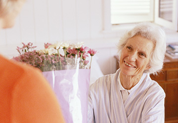 elderly woman smiling at some flowers
