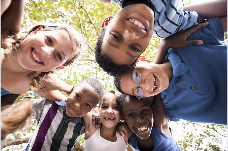 Diverse kids hug circle